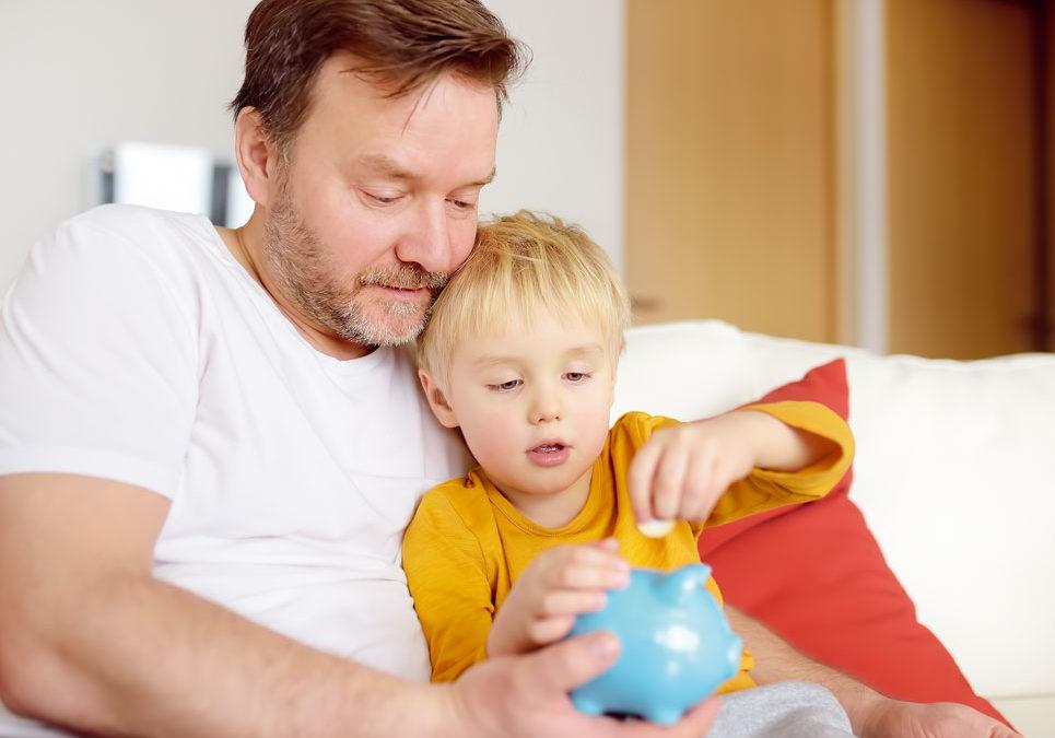 Papa und Sohn werfen gemeinsam Geld in ein Sparschwein