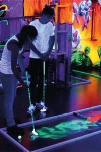 Ein Mann und eine Frau spielen Minigolf im Schwarzlicht
