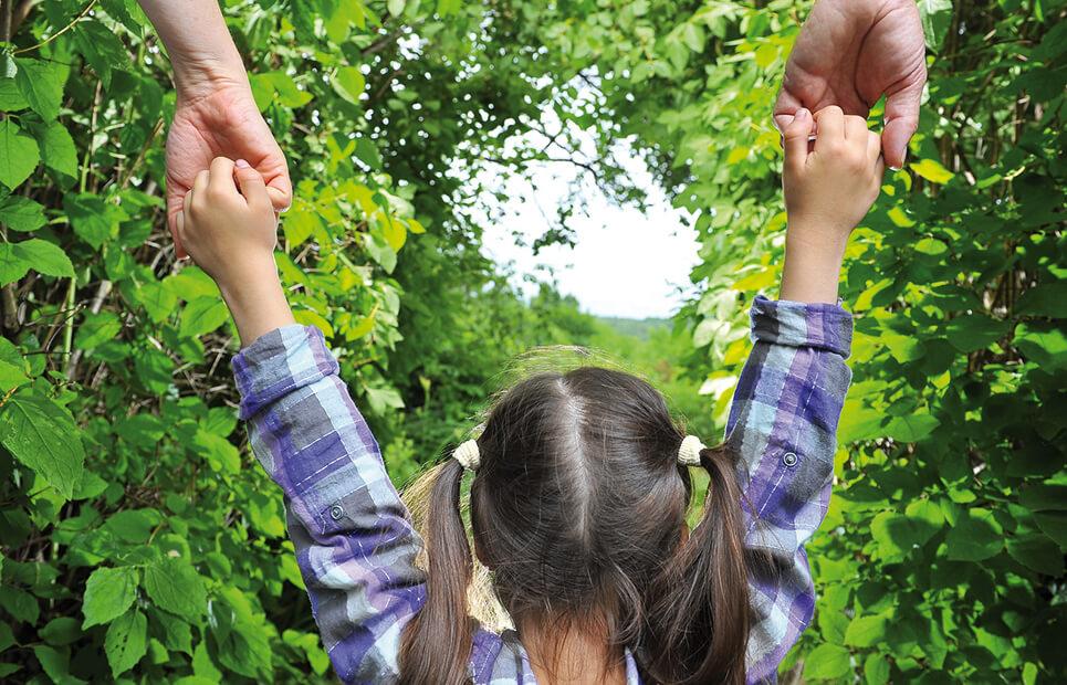 Eltern haben ihr Kind zwischen sich an der Hand.