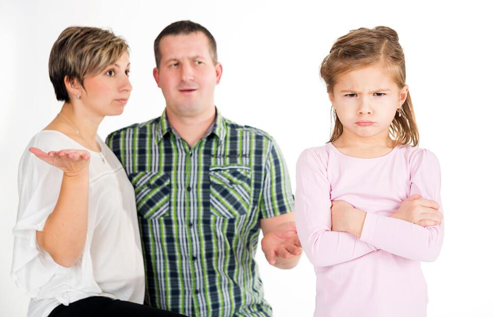 Trotziges Mädchen, Eltern stehen im Hintergrund