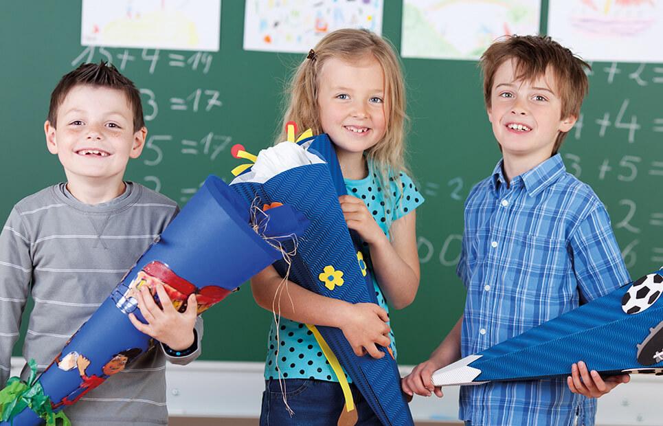 Drei Kinder mit Schultüte in einem Klassenzimmer vor einer Tafel