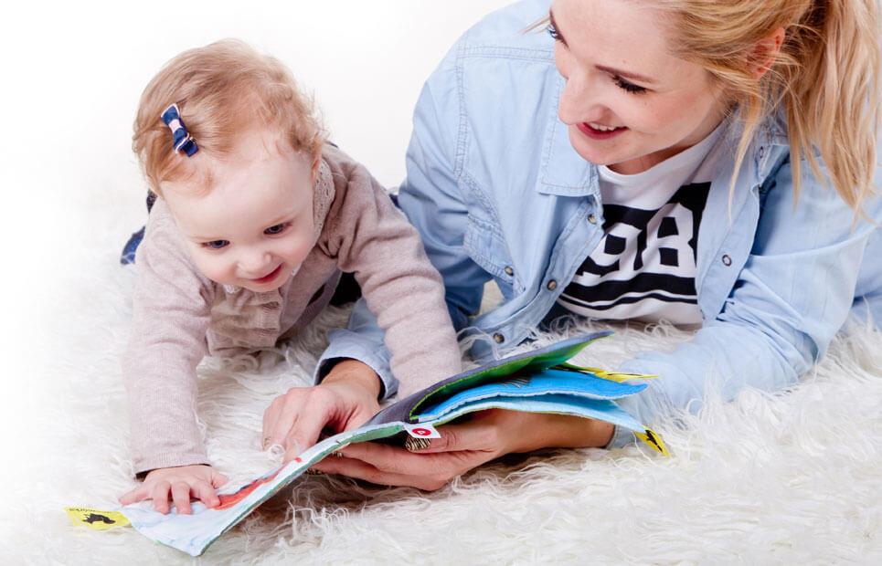 Mutter betrachtet Bilderbuch gemeinsam mit Baby