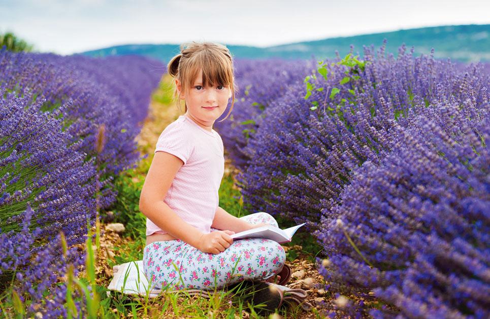 Mädchen sitzt in Lavendelfeld