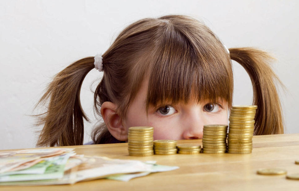 Kind hinter Geldmünzen auf Tisch