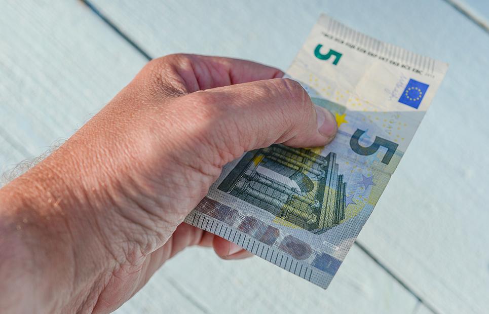 Mann überreicht 5 Euro-Schein