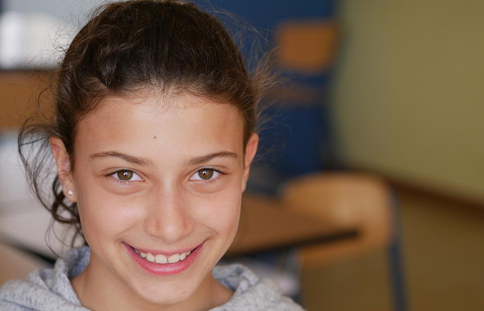 Mädchen blickt lächelnd in die Kamera