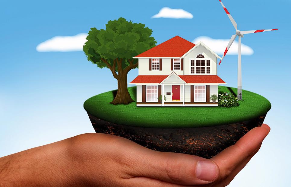 Hand hält ein Stück Erde, darauf ein Haus und Windrad