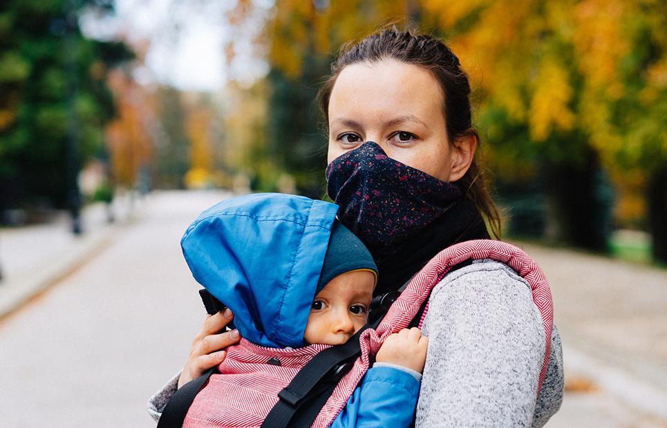 Mutter mit Maske trägt Baby