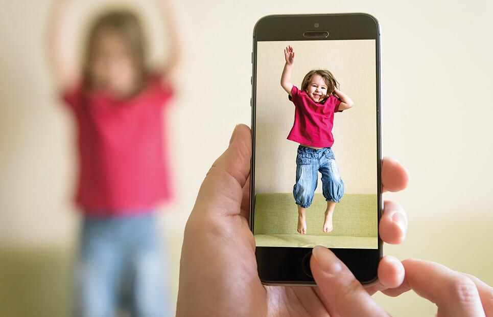 Erwachsene Person die ein Kind mit einem Handy fotografiert