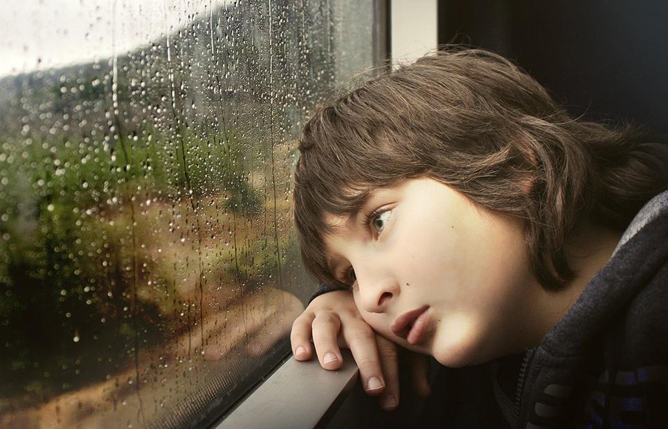 Junge blickt traurig aus dem Fenster