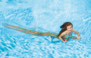 Mädchen mit Meerjungenfrauenfloss im Wasser