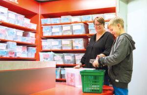 Ein Junge sucht Geschenke für seinen Geschenkekorb im Spielwarengeschäft aus