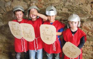 Vier Kinder mit selbst gebastelten Ritterhelmen und Schildern