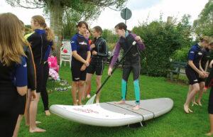 Ein Mädchen im Teenageralter macht eine Trockenübung auf einem Stand Up Paddle Board