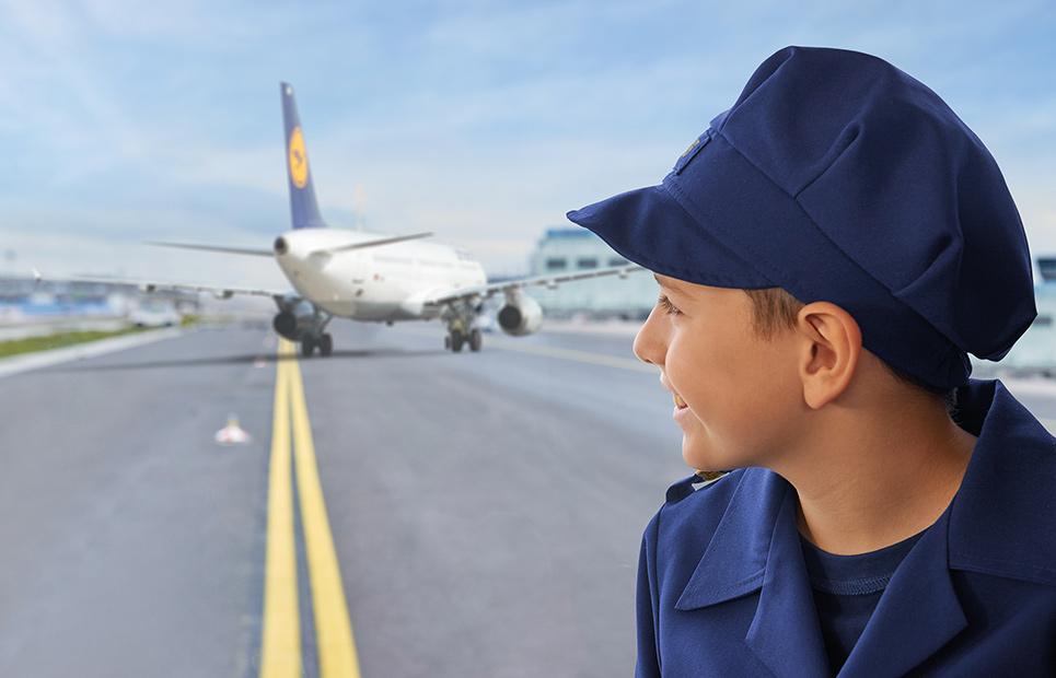 Eine Junge schaut auf ein Flugzeug der Lufthansa, das auf dem Rollfeld steht