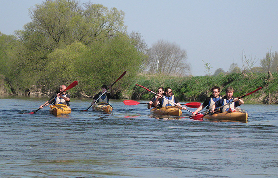 Mehrere Kanufahrer paddeln auf der Lahn