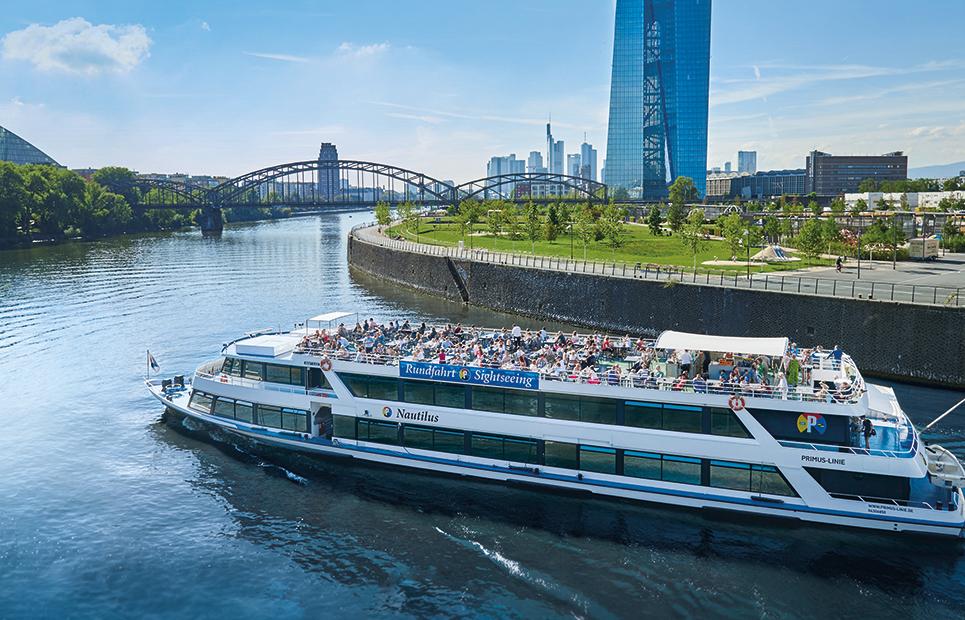 Ein Schiff bei einer Stadtrundfahrt auf dem Main. Im Hintergrund die Frankfurter Skyline.